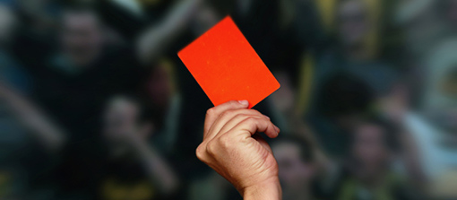 referee holds a red card