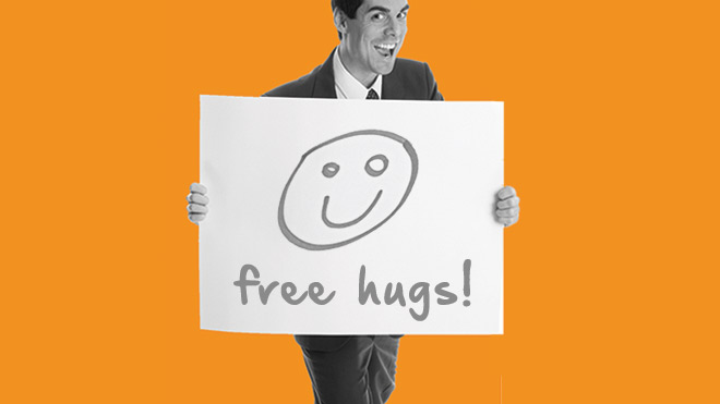 Photo of a man wearing a suit and holding up a sign that says: free hugs