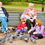 Grandparents with children, feeding birds in London