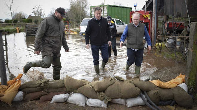 David Cameron standing in floodwater