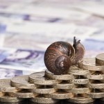 Snail climbing a pile of pound coins