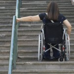 Woman climbing a flight of stairs in a wheelchair