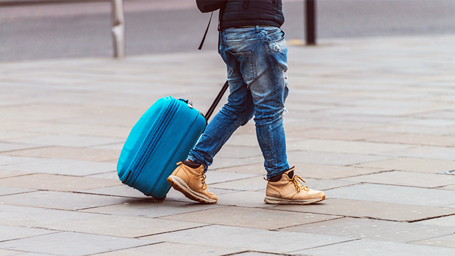 Image of person walking down a street with a suitcase