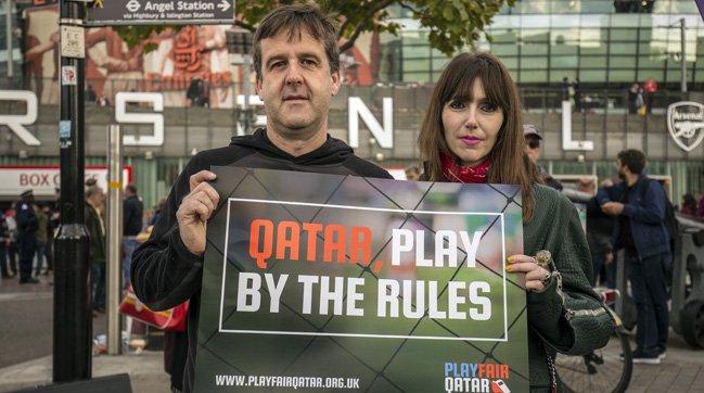 "A man and a woman, chairs of two Arsenal supporters' groups, hold a ""play by the rules"" sign outside the Emirates stadium."