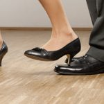 woman in heels steeping on male colleague's foot